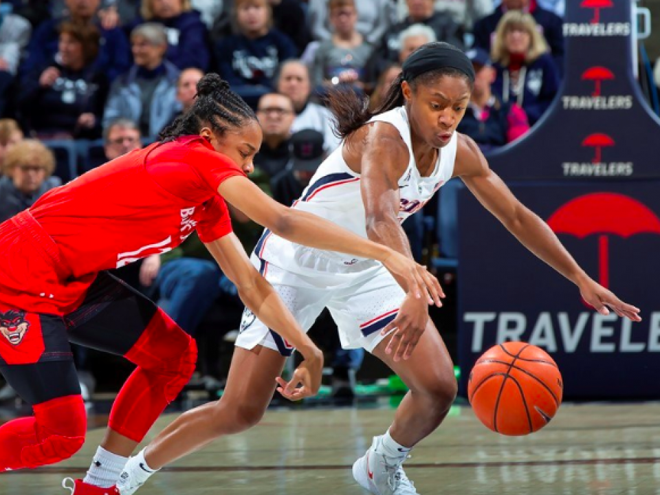 Crystal Dangerfield get away from a defender in a game for UConn women's basketball