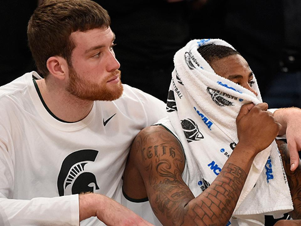 Keith Appling, right, watches from the bench as his collegiate career comes to an end.