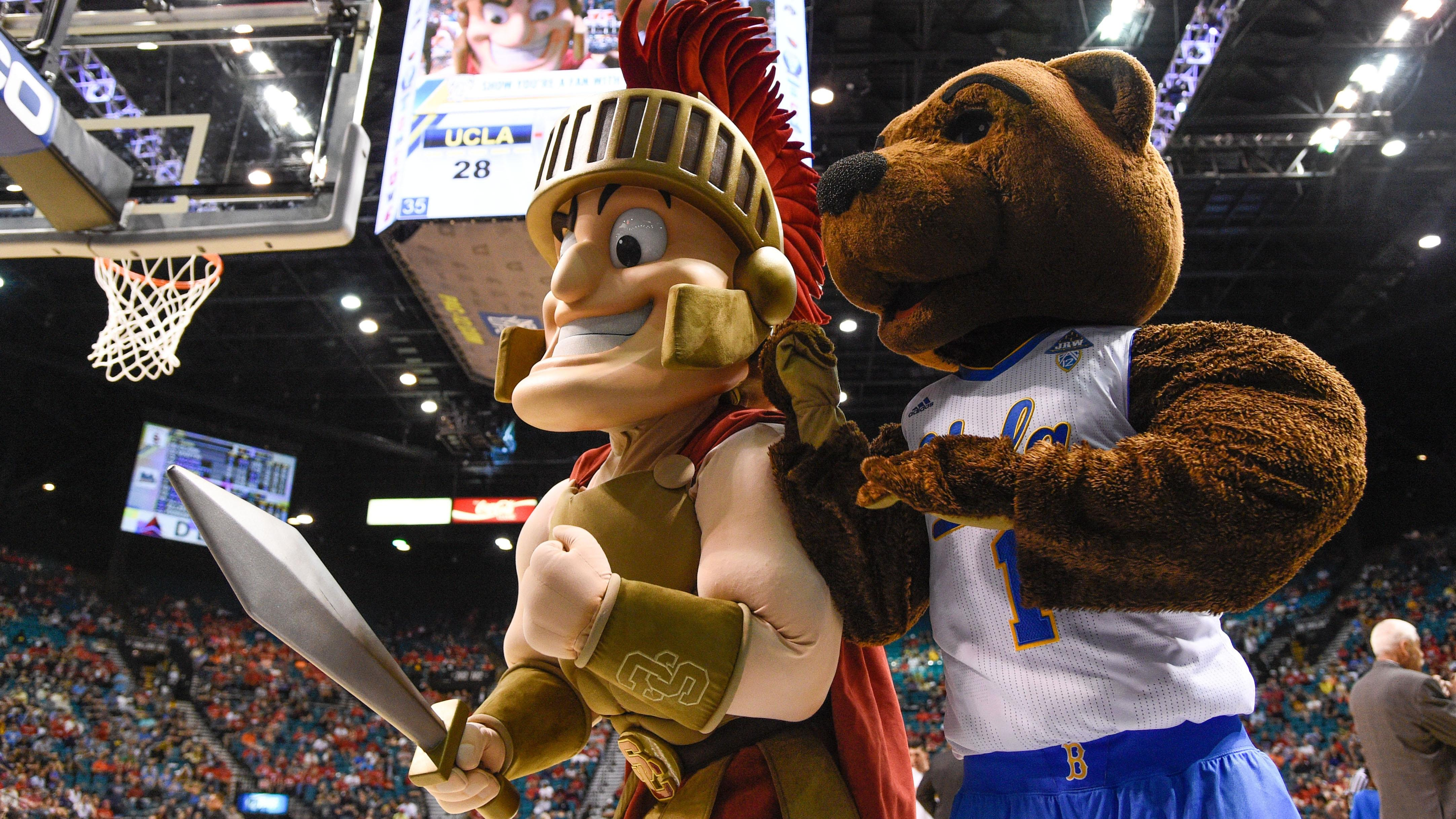 The mascots for USC and UCLA pose at a basketball game.